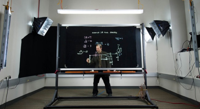 a man doing math on a whiteboard